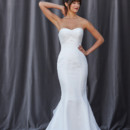 FINLEY A fit and flare gown that has an intricately pleated sweetheart neckline and distinct ruffle train with buttons along the top of the train.