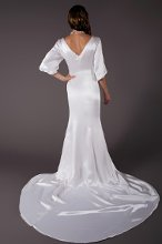 Victoria Silk satin bias trumpet gown in ivory with a bateau neckline, V-back, and a pleated panel at center of ¾ asymmetrical bubble sleeves. Victoria features a chapel train, and is fully lined in ivory silk-charmeuse.