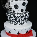 A twist on the traditional black and white wedding cake with carved sides to give the cake a whimsical feel - and then a pop of color with the red bow!