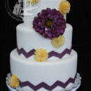 Fondant-covered cake with eggplant purple chevron pattern and silk flowers.