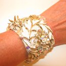 Creamy white, vintage jewelry embellished cuff bracelet. Fabulous combination of enamel flora and fauna with aurora boreallis rhinestones. 2 inches wide, covered in cream silk dupione. For sale on etsy: https://www.etsy.com/listing/101883668/cream-bride-wedding-leaf-floral-flower