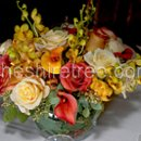 A centerpiece of roses, calla lilies and mokara orchids in sunset colors is perfect for any time of year.