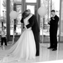130x130 sq 1463076656903 atrium ceremony gray bride and groom kiss