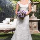 "Style 1942 Soft and chic describes this gown which is accented with sheer cap sleeves and plunging deep ""V"" shaped back neckline. The gown is trimmed with scalloped Chantilly lace appliqués and the bodice features a silk band and beaded flower appliqué."