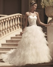 Style 2114 Layers of tiered tulle create this ball gown. Sweetheart neckline and ruched bodice has beadwork, silver embroidery, and 3-dimensional tulle flowers accenting the front and back. Satin sash trims the waist seam.