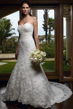 Style 1914 Dazzling and romantic this strapless gown has a trumpet silhouette and a semi-cathedral length train. This gown features beautifully beaded Alencon lace appliques hand sewn onto point d'esprit and a ruched sweetheart bust line. This gown will surely flatter her figure!