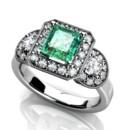 Custom three stone emerald engagement ring. Diamond halos and half moon cut diamonds on each side. Vintage look with mill grain.