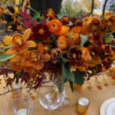Grace Kim Floral & Event Design- orange & gold centerpiece: cymbidium orchids, marigolds, weber tulips, ranunculus, sage, japanese maple branches, bittersweet branches