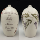 "Wedding Wish Vase© hand formed and painted porcelain vase to receive your keepsake messages. Featuring ""Wisteria"" decoration with purple flowers and green leaves and vines. Personalized with the couples' names and wedding date. Comes with poem encouraging heartfelt notes from wedding guests. Easily opened becoming a treasured keepsake."
