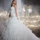 Style 15546 is a stunning and beautiful strapless organza gown with a beaded bodice. The gown then continues into a dropped waist and a voluptuous ruffled skirt.