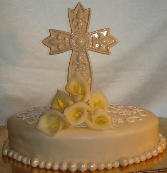 1229052041814 Fondantcoveredcakewithceramiccross,whitechocolatecallalilliesandpearlborders Greenville wedding cake