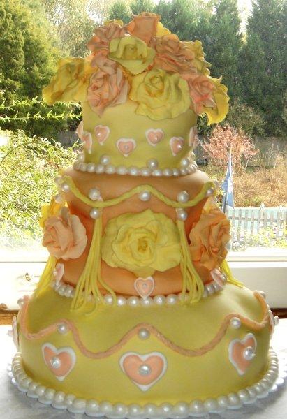1229052276142 Threetierweddingcakewithorangeandyellowroses,sugarsculpturehearts,pearlsandtassels Greenville wedding cake
