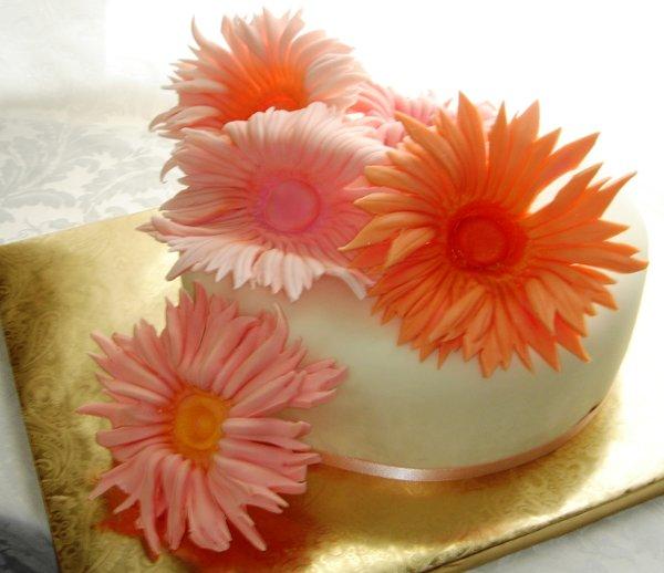 1229378170306 Easterfondantcakewithlargepinkandorangedaisies Greenville wedding cake