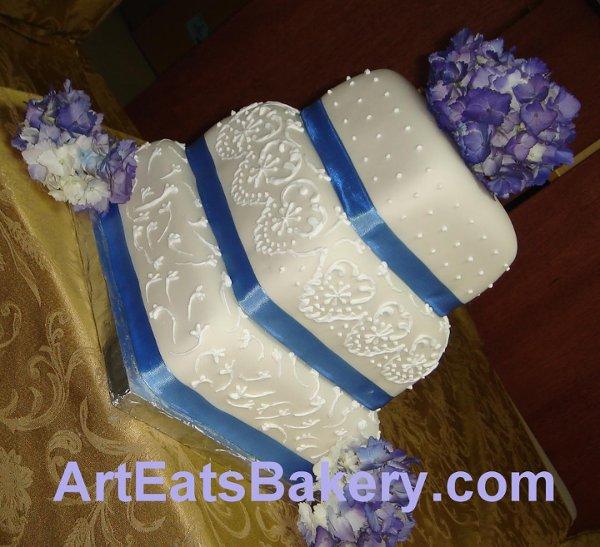 1242612163609 Squarefondantweddingcakewithblueribbonspurpleflowersandroyalicingpiping Greenville wedding cake