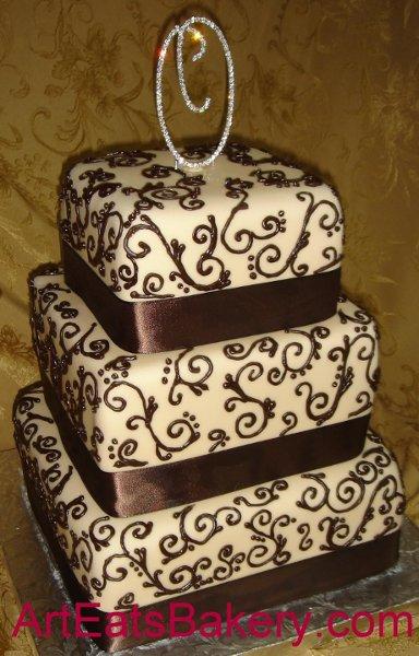1249953275350 Threetiersquareweddingcakewithchocolatebrownribbonsandscrolls Greenville wedding cake