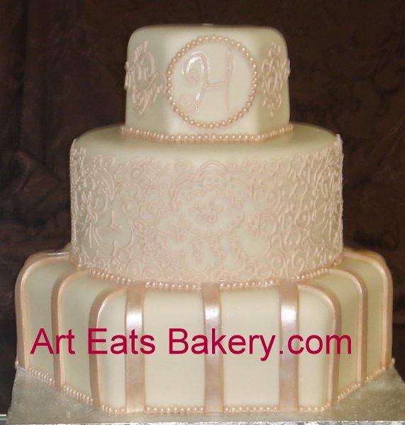 1279494557687 Customroundandhexagonivoryandchampagnemonogramandlacefondantweddingcake Greenville wedding cake