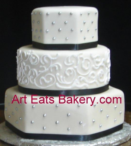 1279494622062 Threetierwhitefondantcustomhexagonandroundweddingcakewithsilverdotsandblackribbons Greenville wedding cake