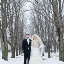 130x130 sq 1402079331596 bride and groom stand in snow under snow covered t
