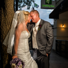 220x220 sq 1494435959156 bride and groom embrace in front of hotel