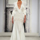 Style 32813651  This sheath gown features a v-neck neckline with in silk chiffon and lace. It has a sweep train and 3/4 length sleeves. This gown is Exclusive to Kleinfeld Bridal.