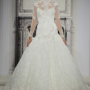 Style # 32813560 This ball gown features an high neck neckline with a dropped waist in beaded lace. It has a chapel train and long sleeves. This gown is Exclusive to Kleinfeld Bridal.