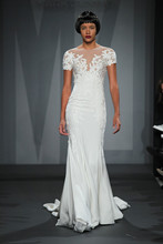 Style 32818114  This sheath gown features an illusion neckline with in silk crepe and lace. It has a chapel train and cap sleeves. This gown is Exclusive to Kleinfeld Bridal.