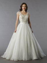 Style 32797540 This ball gown features a scoop neckline with a natural waist in tulle and beaded embroidery. It has a chapel train and cap sleeves. This gown is Exclusive to Kleinfeld Bridal.