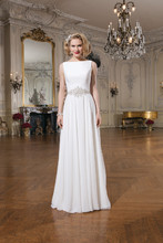 Style 8733 Chiffon A-line gown featuring a Sabrina neckline with an attached pearl and crystal band at the natural waist over a flowy circular chiffon skirt. The gown is finished with chiffon covered and crystal buttons to the end of the chapel length train.