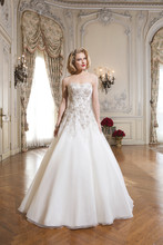 Style 8738 Heavily beaded metallic embroidered lace over organza A-line gown. The gown features a soft sweetheart neckline and is finished with crystal and tulle covered buttons over the back zipper and a chapel train.