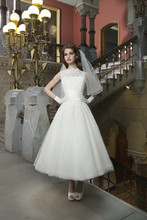 Style 8706 Alencon lace and tulle tea length ball gown features a Sabrina neckline and silk dupion criss-cross pleated cummberbund. The back of the gown has a V-back neckline and silk dupion buttons.