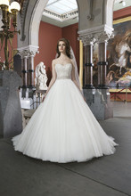 Style 8724 Tulle ball gown features intricately beaded bodice with a sweetheart neckline. Style has a chapel length train and regal satin buttons to cover the back zipper. This style includes a detachable beaded belt at the natural waistline.