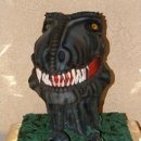 T-Rex groom's cake - Hand sculpted, hand painted and airbrushed. Chocolate Fudge Cake, Fudge Icing and filling, Chocolate Fondant. All edible, delicious cake! He was a Rock Star!