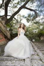 8504  Ivory Tulle bridal ball gown, lace bodice with halter neckline, T -strap back, sweep train.
