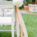 Guests sat in white folding padded chairs lined with ribbon aisle markers.   Venue: Lake Eden Events  Event Planner: Jessica Wharton  Rentals: Classic Event Rental  Floral Designer: Two Buds and A Blossom