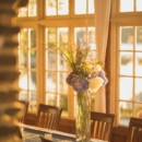 Tables were decorated with custom-made linens, cylinder vase centerpieces, and votive candles, surrounded by wooden dining room chairs.   Venue: The Captain's House  Caterer/Cake: Cocoa Pesto Catering