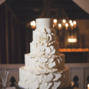 The four-tiered fondant-frosted cake featured cascading sugar flowers.   Cake: Pearl's Cupcake Shoppe