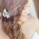 Heather wore her hair down in loose curls with a birdcage veil.  Dress Designer:Lis SImonfromSophia's Bridal Boutique  Hair Stylist: David Moran of Bobby Cooper Salon