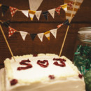 The square buttercream-frosted cake was topped with a bunting banner.  Venue: D Barn