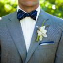 The accessorized a gray textured suit with a navy and white striped bow tie, a navy bordered pocket square, and a green and white boutonniere.  Venue: Atwood Ranch  Event Planner: Julie Atwood Events  Floral Designer: Anne Appleman Flowers & Plants