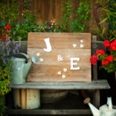 A barnwood sign with Jen and Egan's initials displayed on a rustic garden bench.  Venue: Atwood Ranch  Event Planner: Julie Atwood Events  Floral Designer: Anne Appleman Flowers & Plants