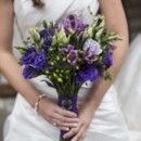 The bride's bouquet featured lisianthus and berries.   Ceremony Venue: Pulaski Square  Event Planner/Floral Designer: Coastal Creative Events   Hair and Makeup Artist: Beyond Beautiful