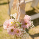 The aisles were marked with mason jars filled with pink daisies, baby's breath, and waxflower.  Venue: Shady Wagon Farm  Event Planner: Happily Ever After  Floral Designer: Skyland's Florist