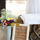 A haystack bench surrounded by a giant ampersand, a social media sign, a tin flower bucket filled with fun photo booth props, and a baby's breath arrangement.  Venue: Shady Wagon Farm  Event Planner: Happily Ever After  Floral Designer: Skyland's Florist