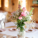 Mason jars filled with snapdragons, roses, waxflower, fern, and baby's breath, wrapped in lace and twine, and displayed on tree slices.  Venue: Shady Wagon Farm  Event Planner: Happily Ever After  Floral Designer: Skyland's Florist