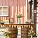 A wine barrel table draped with a burlap pennant