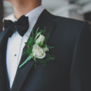 Ray accessorized with a velvet bow tie and an ivory spray rose and greenery boutonniere.  Venue:Atlantis  Groom Attire:Harry Rosen  Floral Designer:Four Season Flowers
