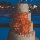 A four-tier wedding cake decorated with iced swiss dots and a glamorous orange fondant flower.  Venue: Atlantis  Cake: Cheerful Tiers