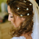 The bride wore her wavy hair half-up, embellished with mini flowers.  Venue: Ktima Laas  Dress Designer:Christos Costarellos