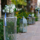 The estate pathways were lined with elegant garden lanterns topped with petite arrangements of roses, ranunculus, baby's breath, and bear grass.  Venue: Ktima Laas