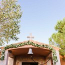 A charming, historic chapel adorned with in greenery and white blooms.  Venue: Ktima Laas